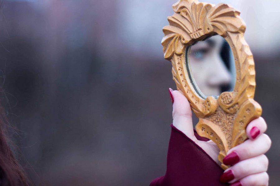 girl stares into mirror