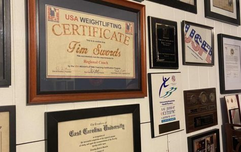 Local legend Tim Swords coaches weightlifting in his garage. He hands various accolades and awards on his garage wall.